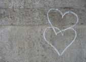 2 hand drawn white chalk love hearts on a grungy gray concrete w — Stock Photo