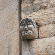Stone face on brichwall. - Stock Photo