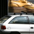 Car with big shoe on the roof — Stock Photo