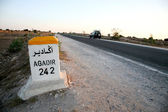 Sign road with distance to agadir — Stock Photo