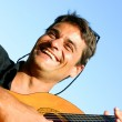 Cute young man playing guitar and smiling — Stock Photo