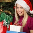 Blond female holding Christmas presents — Foto Stock