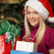 Blond female holding Christmas presents - Stockfoto