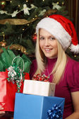 Blond female holding Christmas presents — Stockfoto