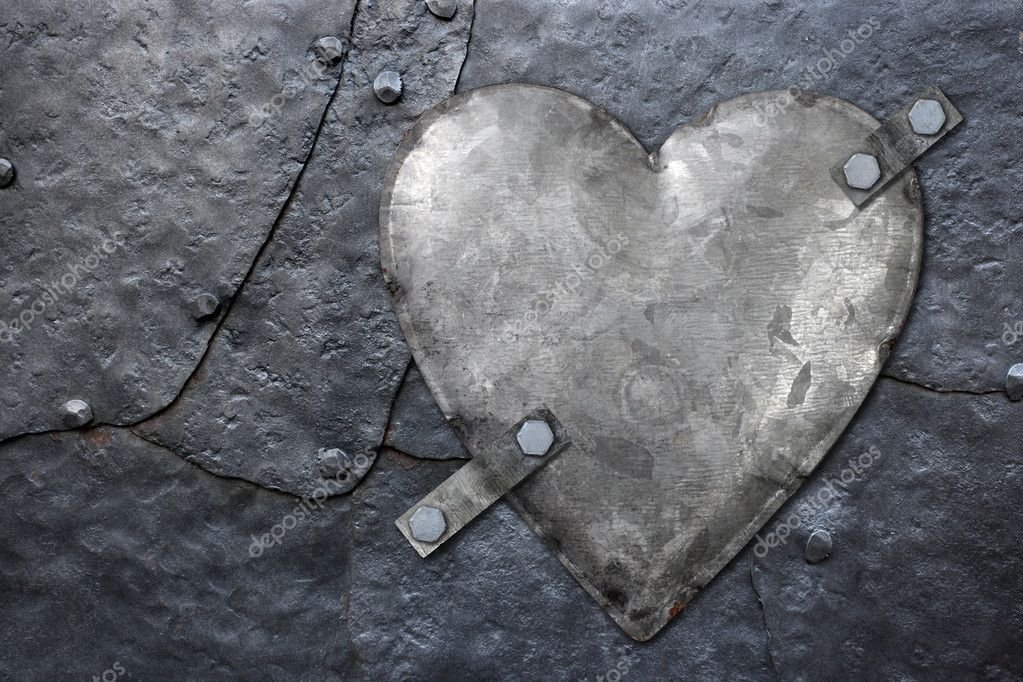 Photo of a galvanized metal heart bolted to old hammered metal plates with rivets.  Stock Photo #4687321