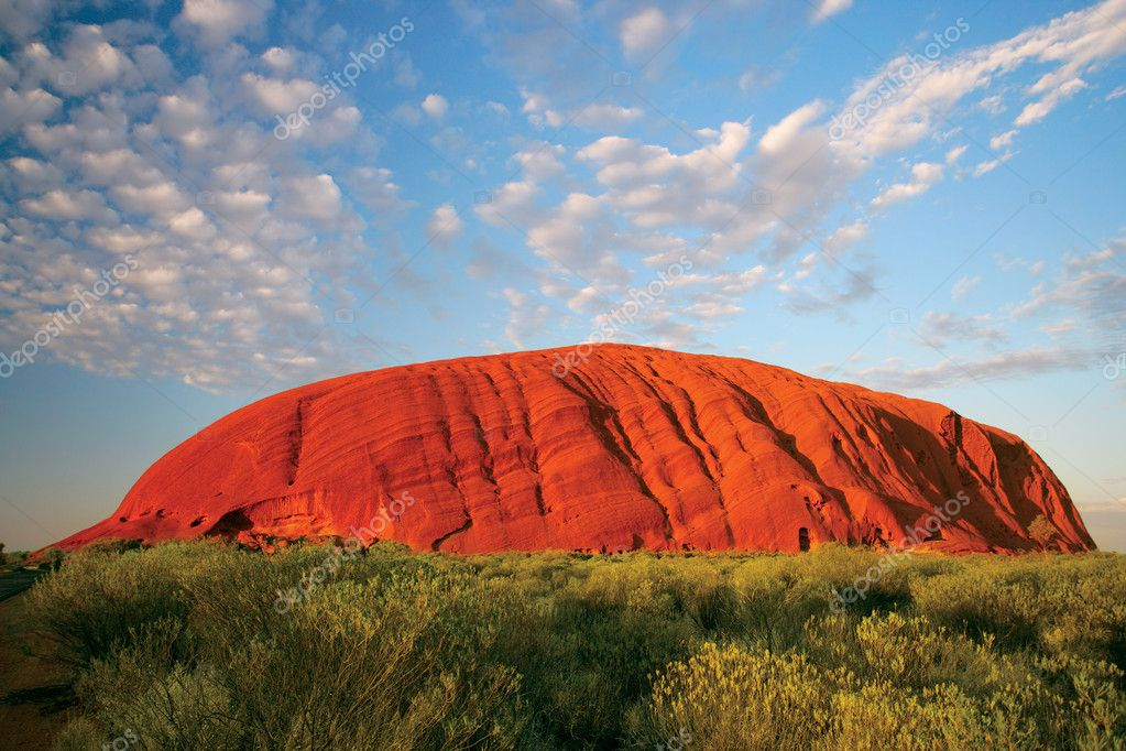 Ayers Rock in Australia early in the morning as the sun turns the rock bright red. — Stock Photo #4819923