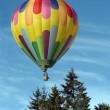 Hot air balloon above the trees — Stock Photo
