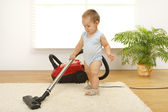 Baby boy with vacuum cleaner — Stockfoto