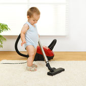 Baby boy with vacuum cleaner — Stock Photo