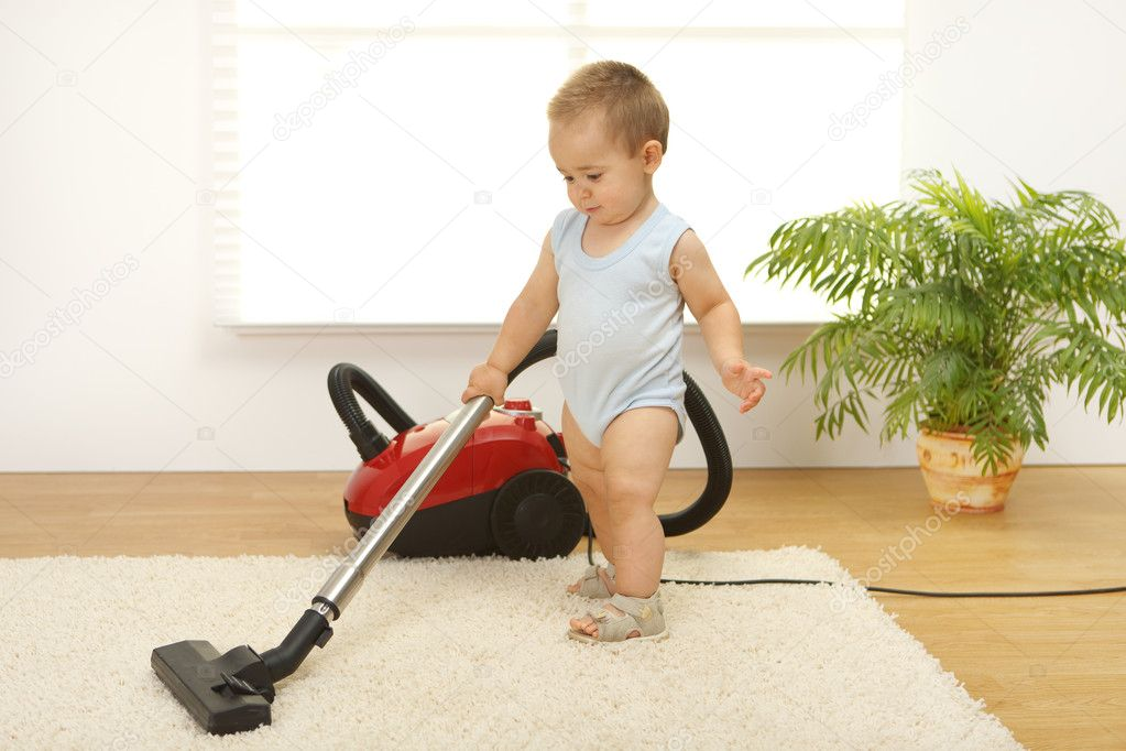 Baby boy cleaning the carpet with vacuum cleaner — Stock Photo #4011532
