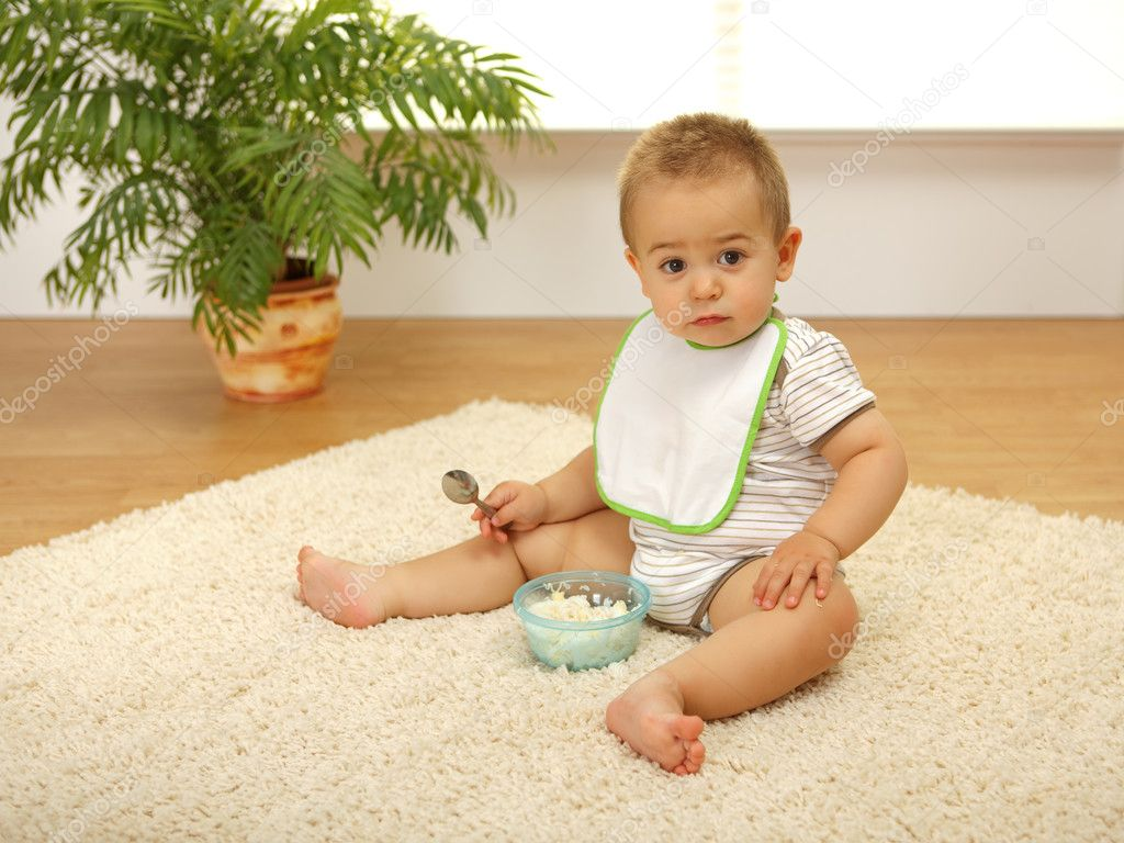 Little baby boy sitting alone on white carpet and eating — Stock Photo #4011558