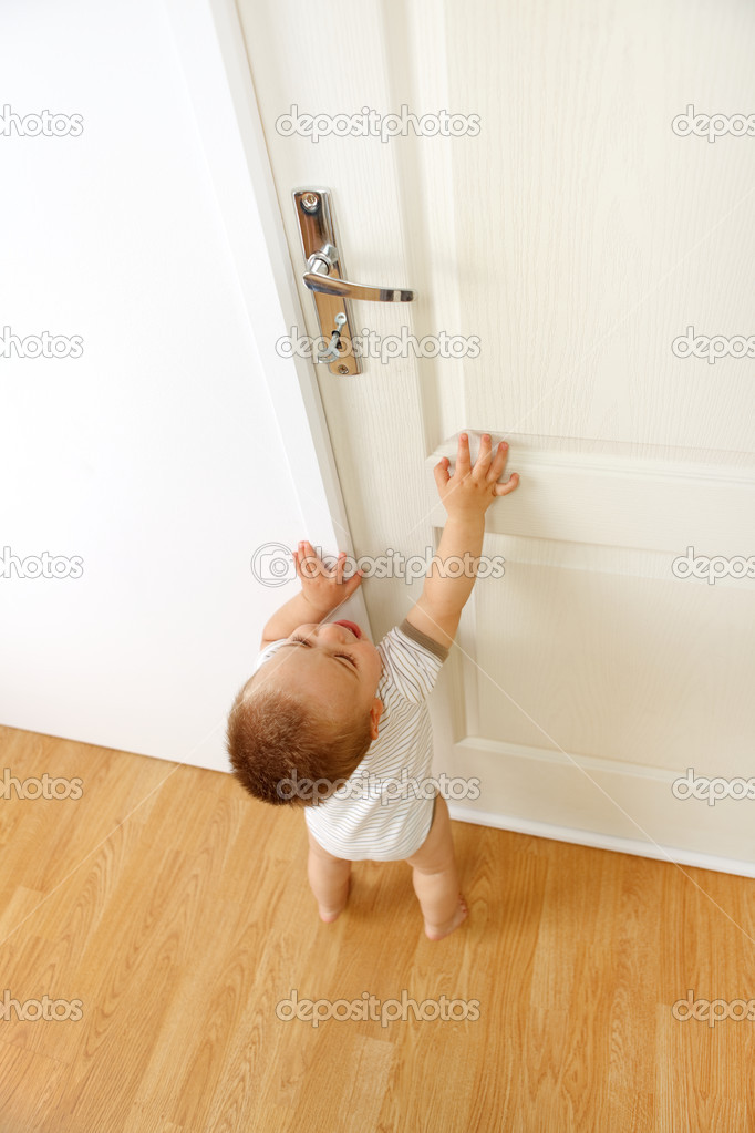 Baby boy crying, wants to reach the door handle. Conceptual view of being out of reach because of being too small for something — Stock Photo #4011619
