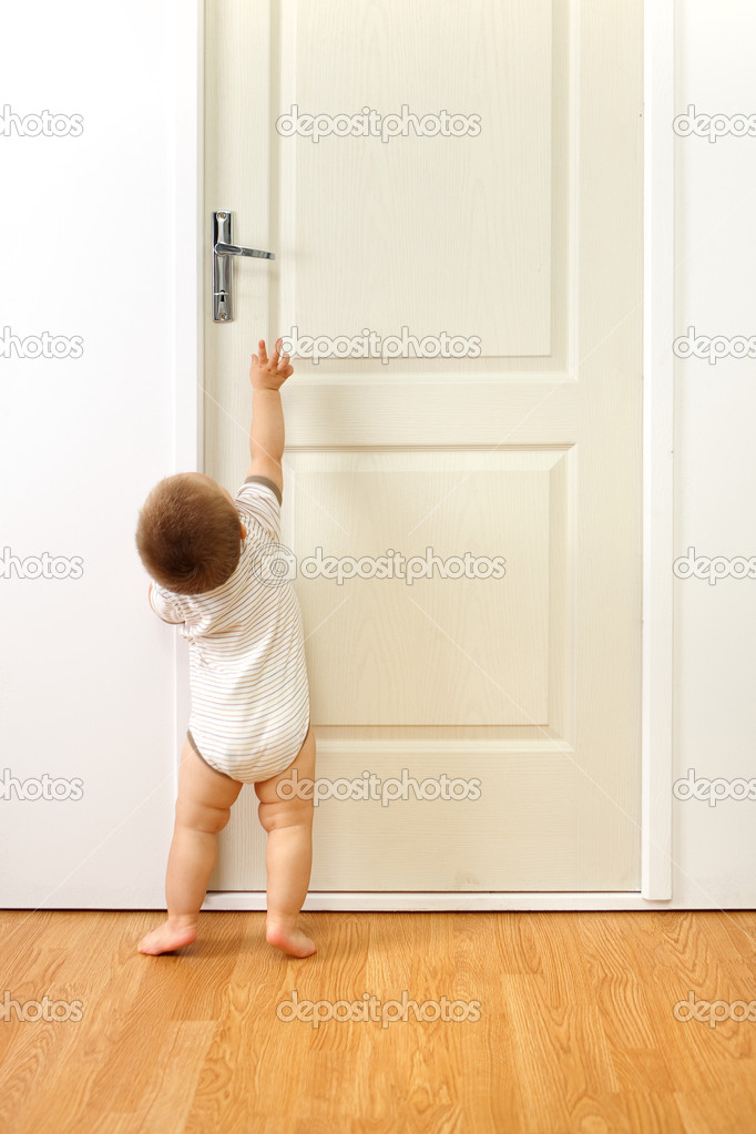 Baby boy in front of a closed door, trying to reach the handle — Stock Photo #4011897