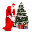 SantClaus putting gifts under christmas tree — Foto Stock #4189954