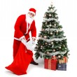 Santa Claus putting gifts under christmas tree — Stock Photo