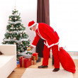 Santa Claus putting gift under christmas tree — Stock Photo