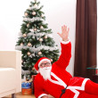 Santa claus laying on floor in front of christmas tree — Stock Photo