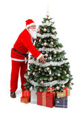 Santa Claus holding Christmas tree — Stock Photo