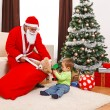 Little boy taking out toys from Santa's bag — Stock Photo