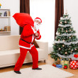 Stock Photo: SantClaus walking with full bag