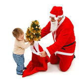 Little boy puts small tree in Santa's bag — ストック写真