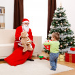 Santa Claus showing toy from bag — Stock Photo #4482725