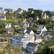 Nice coastal village in sunshine - colored houses on a hill - Stock Photo