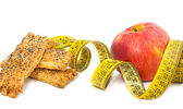 Red apple, cookies and measured metre on a white background — Stock Photo