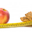 Red apple, cookies and measured metre on white background — Stockfoto #4324351