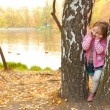 Smiling girl stands between birch trees — Stock Photo