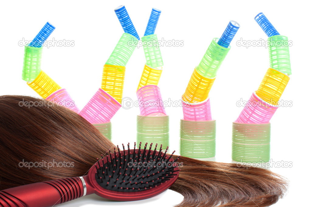 Dark brown and long female hair, red comb and colorful hair curlers at the background. Isolated over white  Stock Photo #5259775