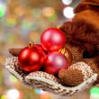 Stock Photo: Hands dressed in mittens hold Christmas balls on abstract col