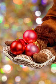 Hands dressed in mittens hold Christmas balls on an abstract col — Stock Photo