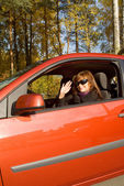 The girl in the red car in an autumn sunny day — Stock Photo