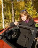 Dziewczyna z kluczem pozostawia czerwony samochód — Zdjęcie stockowe