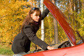 The girl repairs the car motor — Stock Photo