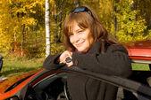 Anahtar olan genç kadın onu yakın: kırmızı araba — Stok fotoğraf