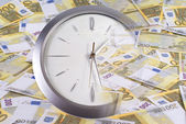 Clock and 200 euro banknotes on a white background — Stock Photo