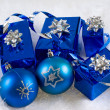 Blue boxes and Christmas blue balls are on the white fur — Stock Photo