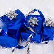 Blue shiny boxes for gifts with silver ribbons on the white skin — Stock Photo