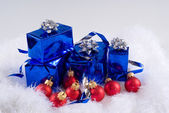 Blue boxes and Christmas red balls are on the white fur — Stok fotoğraf