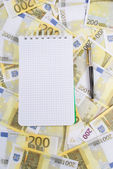 Writing-book with pen on banknotes 200 euros — Stock Photo