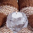 Two hands dressed in mittens hold burning candle — Foto Stock #4298754