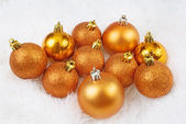 Christmas golden orange spheres on a white fur — Stock Photo