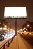 Big white billboard on the night street — Stock Photo