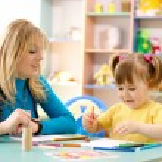 Teacher with child in preschool — Stock Photo