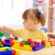 Little girl play with building bricks in preschool - Stock Photo