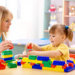 Stock Photo: Teacher and preschooler play with building bricks