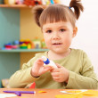 Little girl doing arts and crafts in preschool — Stock Photo #4149742