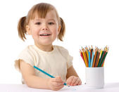 Cute child draws with color pencils — Stockfoto